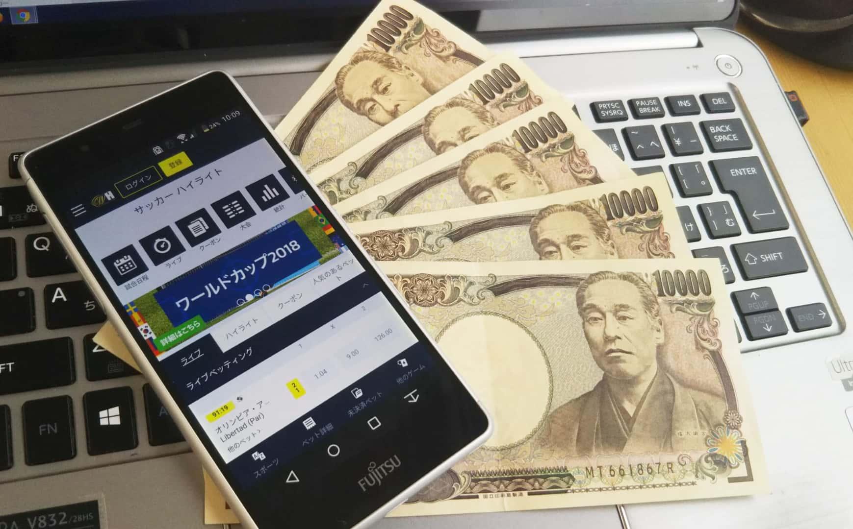 PCの上に置かれたウィリアムヒルが表示されたスマホと1万円札5枚