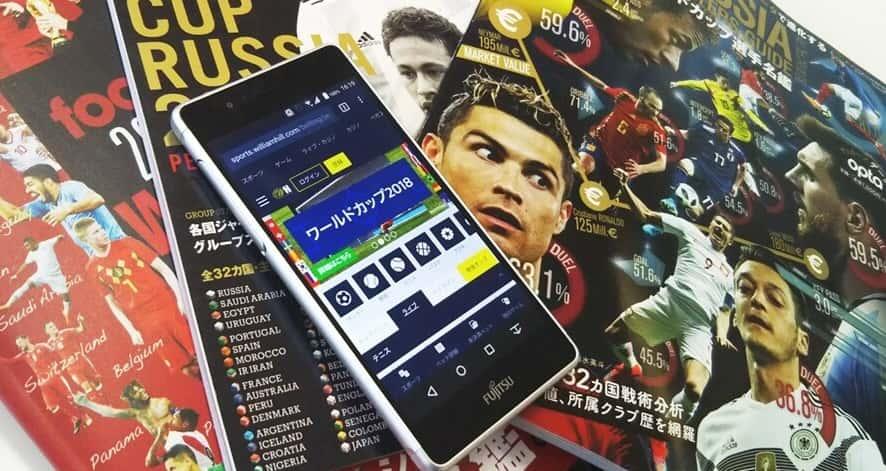 ロシアワールドカップの雑誌の上にウィリアムヒルを表示したスマホを置いた写真