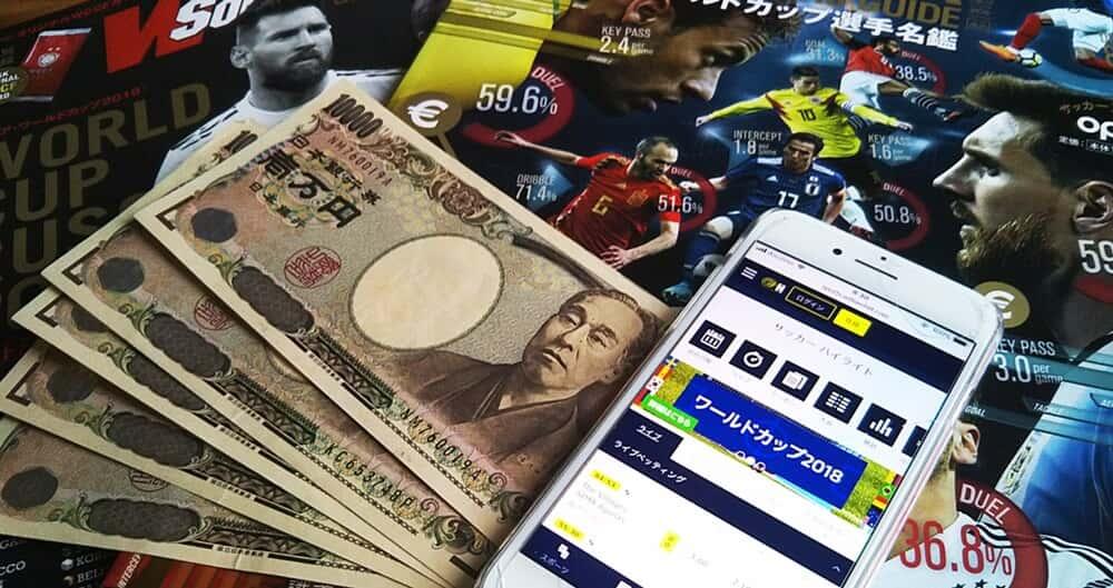 ロシアW杯雑誌の上にウィリアムヒルを表示したiPhoneと1万円札5枚