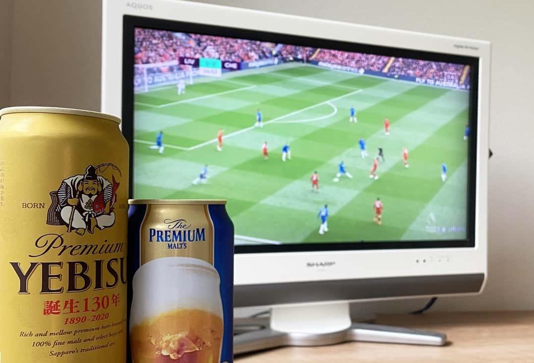 缶ビール2本とサッカー中継を映しているテレビ